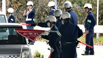 In this April 11, 2018, photo, police officers inspect cars at a checkpoint in Onomichi, Hiroshima prefecture. Japanese police have deployed hundreds of policemen in pursuit of a jail breaker who landed on a tiny island near Hiroshima with abundant hideouts, some 1,000 vacant homes left behind as the island population aged and shrunk. The 27-year-old Tatsuma Hirao has been at large since Sunday, April 8 when he fled from a prison in Ehime prefecture where he was serving his term for his convicted theft. (Shingo Nishizume/Kyodo News via AP)