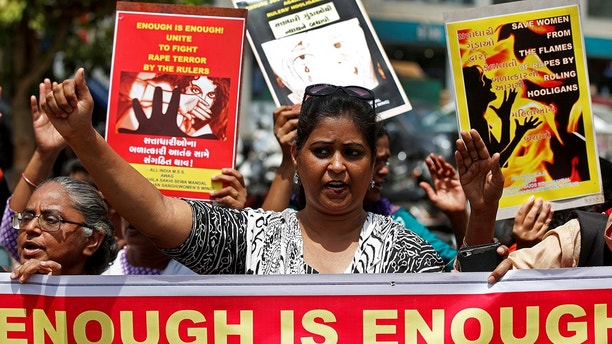 People hold placards at a protest against the rape of an eight-year-old girl, in Kathua, near Jammu and a teenager in Unnao, Uttar Pradesh state, in Ahmedabad, India April 13, 2018. REUTERS/Amit Dave - RC114FAA6000
