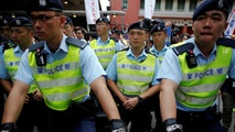 Police monitor pro-independence activists taking part in a march marking the 20th anniversary of Hong Kong's handover to Chinese sovereignty from British rule, in Hong Kong, China July 1, 2017. REUTERS/Damir Sagolj - RC159360E900