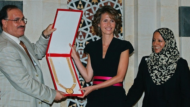 Karim Farman, Chairman of Paris-Based Arab Woman Studies Center (L), and member Shakour Al-Ghomari, give Syria's first lady Asma al-Assad (C) the Center's prize of the Arab First Lady of 2008, in Damascus August 27, 2008. The prize was awarded to al-Assad for her role in sponsoring National projects aimed at enhancing education and development in rural areas in Syria. The prize is awarded in cooperation with the Arab League.REUTERS/Khaled al-Hariri  (SYRIA) - GM1E48S094G01