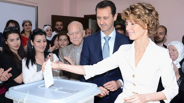 Syria's President Bashar al-Assad and his wife Asma (R) cast their votes in the country's presidential elections at a polling station in Damascus June 3, 2014, in this handout released by Syria's national news agency SANA. Syrians voted on Tuesday in an election expected to deliver an overwhelming victory for al-Assad in the midst of a devastating civil war but which his opponents have dismissed as a charade. REUTERS/SANA/Handout via Reuters (SYRIA - Tags: POLITICS CIVIL UNREST ELECTIONS TPX IMAGES OF THE DAY)   ATTENTION EDITORS - THIS PICTURE WAS PROVIDED BY A THIRD PARTY. REUTERS IS UNABLE TO INDEPENDENTLY VERIFY THE AUTHENTICITY, CONTENT, LOCATION OR DATE OF THIS IMAGE. THIS PICTURE IS DISTRIBUTED EXACTLY AS RECEIVED BY REUTERS, AS A SERVICE TO CLIENTS. FOR EDITORIAL USE ONLY. NOT FOR SALE FOR MARKETING OR ADVERTISING CAMPAIGNS - GM1EA631JUX01