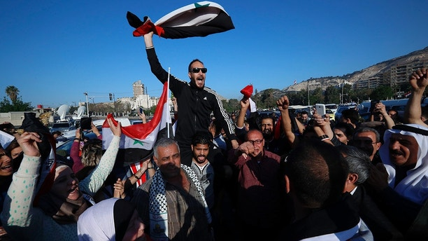 Syrian government supporters chant slogans against U.S. President Trump during demonstrations following a wave of U.S., British and French military strikes to punish President Bashar Assad for suspected chemical attack against civilians, in Damascus, Syria, Saturday, April 14, 2018. Hundreds of Syrians are demonstrating in a landmark square in the Syrian capital, waving victory signs and honking their car horns in a show of defiance. (AP Photo/Hassan Ammar)
