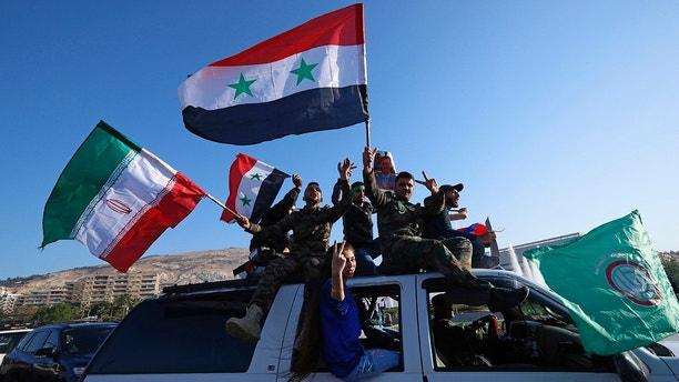 Syrian government supporters wave Syrian, Iranian and Russian flags as they chant slogans against U.S. President Trump during demonstrations following a wave of U.S., British and French military strikes to punish President Bashar Assad for suspected chemical attack against civilians, in Damascus, Syria, Saturday, April 14, 2018. Hundreds of Syrians are demonstrating in a landmark square in the Syrian capital, waving victory signs and honking their car horns in a show of defiance. (AP Photo/Hassan Ammar)