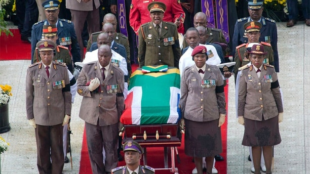 A military honor guard carries anti-apartheid activist Winnie Madikizela-Mandela's coffin, wrapped in the flag of South Africa, out of Orlando stadium following her funeral service, in Soweto, South Africa, Saturday, April 14, 2018. Tens of thousands of people sang, cheered and cried as the flag-draped casket of anti-apartheid activist Madikizela-Mandela was escorted from her official funeral on Saturday, after supporters defended her complex legacy with poetry and anger. (AP Photo/Jerome Delay)