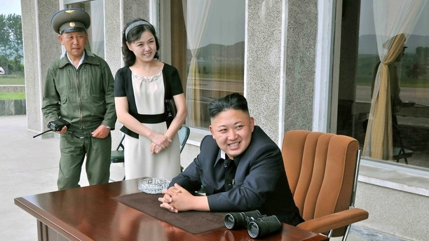 North Korean leader Kim Jong-un (front) and his wife Ri Sol-ju (2nd L) look on during a visit to Unit 1017 of the Korean People's Army (KPA) Air and Anti-Air Force, honoured with the title of O Jung Hup-led 7th Regiment, in this undated picture released by North Korea's Korean Central News Agency (KCNA) on June 21, 2013.     REUTERS/KCNA    (NORTH KOREA - Tags: POLITICS MILITARY TRANSPORT TPX IMAGES OF THE DAY) ATTENTION EDITORS - THIS PICTURE WAS PROVIDED BY A THIRD PARTY. REUTERS IS UNABLE TO INDEPENDENTLY VERIFY THE AUTHENTICITY, CONTENT, LOCATION OR DATE OF THIS IMAGE. FOR EDITORIAL USE ONLY. NOT FOR SALE FOR MARKETING OR ADVERTISING CAMPAIGNS. NO THIRD PARTY SALES. NOT FOR USE BY REUTERS THIRD PARTY DISTRIBUTORS. THIS PICTURE IS DISTRIBUTED EXACTLY AS RECEIVED BY REUTERS, AS A SERVICE TO CLIENTS - GM1E96L0LMU01
