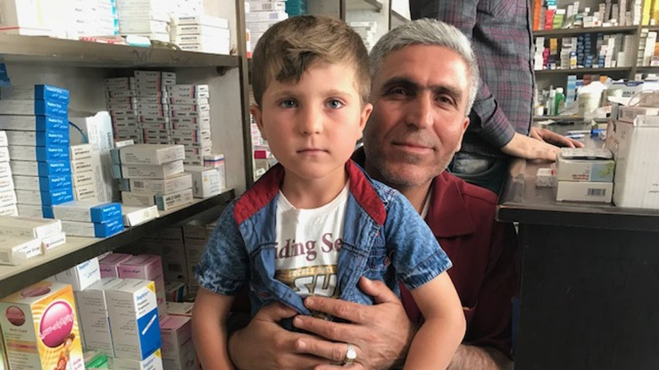 Rezgar Ramadan holding his five-year-old son, Trump, who was renamed after the 2016 presidential election.