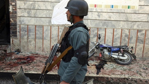 An Afghan police officer stands outside a voter registration center which was attacked by a suicide bomber in Kabul, Afghanistan, Sunday, April 22, 2018. Gen. Daud Amin, the Kabul police chief, said the suicide bomber targeted civilians who had gathered to receive national identification cards. (AP Photo/Rahmat Gul)