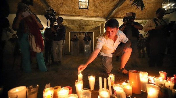 A man lights up a candle during a vigil in memory of three film students that were kidnapped and killed by gunmen after being confused with members of a rival gang, outside the governor's official residence, in Guadalajara, Mexico April 23, 2018. Picture taken April 23, 2018. REUTERS/Stringer NO RESALES. NO ARCHIVES. - RC11AC7FCD00
