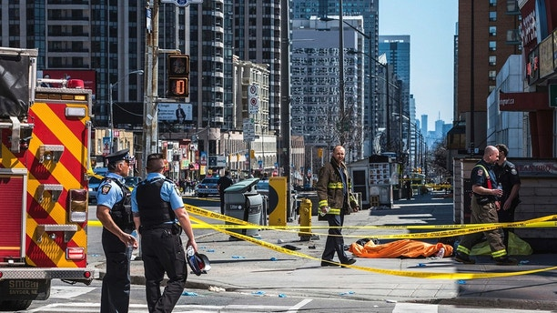 A body lies covered on the sidewalk in Toronto after a van mounted a sidewalk crashing into a number of pedestrians on Monday, April 23, 2018.A van apparently jumped a curb Monday in a busy intersection in Toronto and struck numerous people and fled the scene before it was found and the driver was taken into custody, Canadian police said.  (Aaron Vincent Elkaim/The Canadian Press via AP)