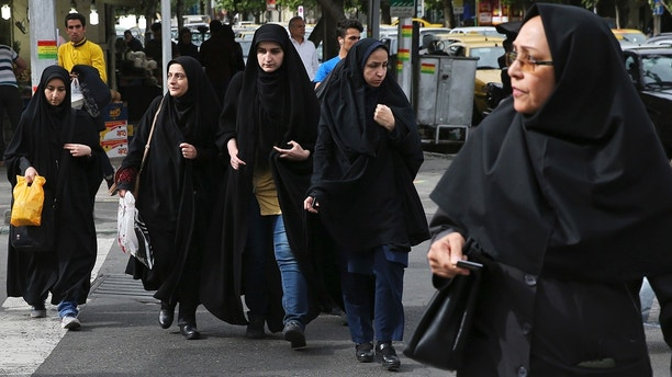 In this Sunday, April 22, 2018, photo, head-to-toe veiled Iranian women cross a street in Tehran, Iran. A grainy video of female officers from Iran's morality police assaulting a young woman whose headscarf only loosely covered her hair has sparked a new public debate on the decades-long requirement for women in the Islamic Republic. (AP Photo/Vahid Salemi)