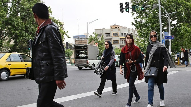 In this Sunday, April 22, 2018, photo, pedestrians cross a street in downtown Tehran, Iran. A grainy video of female officers from Iran's morality police assaulting a young woman whose headscarf only loosely covered her hair has sparked a new public debate on the decades-long requirement for women in the Islamic Republic. (AP Photo/Vahid Salemi)
