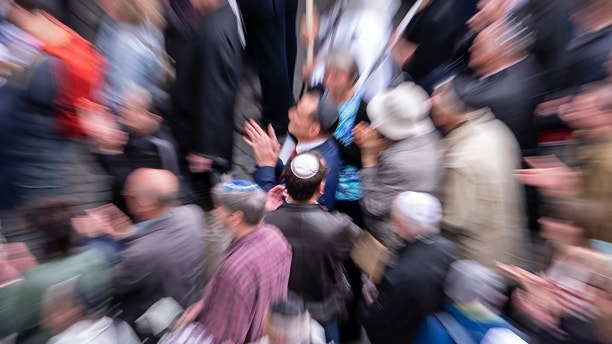 In this zoomed and long time exposure picture people of different faiths wear the Jewish kippah during a demonstration against antisemitism in Germany in Erfurt, Germany, Wednesday, April 25, 2018.  (AP Photo/Jens Meyer)