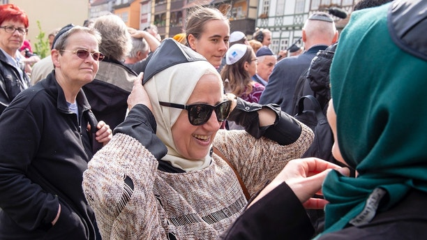 Muslim woman Samar Allaham, center, fixes the Jewish kippah  on her head besides the Muslim woman Iman Jamous, right, during a demonstration against antisemitism in Germany in Erfurt, Germany, Wednesday, April 25, 2018.  (AP Photo/Jens Meyer)