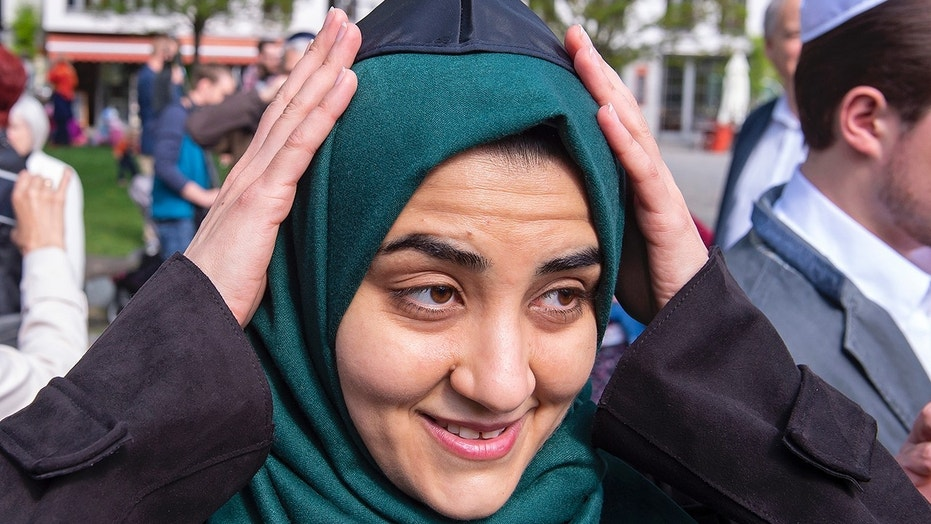 Muslim woman Iman Jamous fixes the Jewish kippah on her head during a demonstration against antisemitism in Germany in Erfurt, Germany, Wednesday, April 25, 2018. (AP Photo/Jens Meyer)
