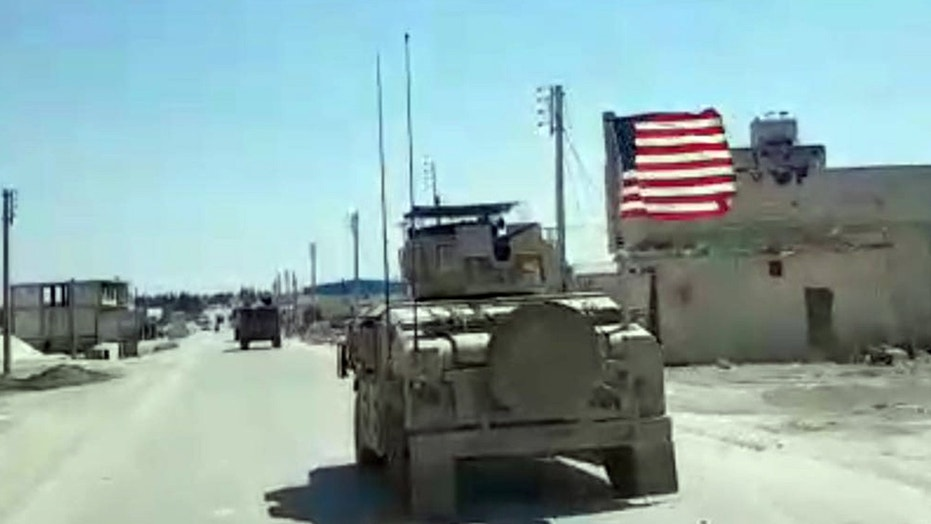 A U.S. humvee rumbles down the street in Manbij, one of the bases of operation for American troops in Syria.