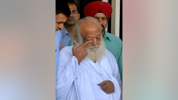 FILE- In this Sept. 1, 2013 file photo, controversial spiritual guru Asaram Bapu, center, is brought for interrogation by police in Jodhpur, India. An Indian court has held the high-profile guru guilty of raping a teenage female devotee in 2013. The verdict against Bapu, 77, was read out inside a prison in the city of Jodhpur in Rajasthan on Wednesday, April 25, 2018, because of fears that his followers may resort to violence. (AP Photo/Sunil Verma, File)