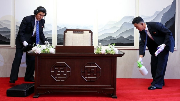 North Korean security officers check and prepare a desk before North Korean leader Kim Jong Un signs a guestbook at the truce village of Panmunjom inside the demilitarized zone separating the two Koreas, South Korea, April 27, 2018.   Korea Summit Press Pool/Pool via Reuters     TPX IMAGES OF THE DAY - RC18FFC9A820