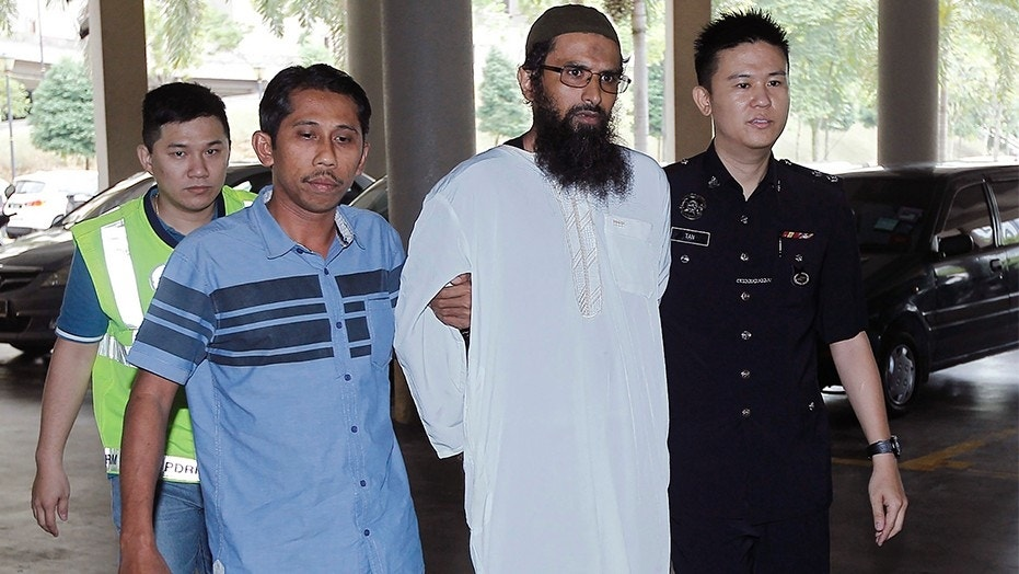 April 30, 2018: Danish national Salah Salem Saleh Sulaiman, second from right, escorted by police, arrives at a court house in Kuala Lumpur, Malaysia.