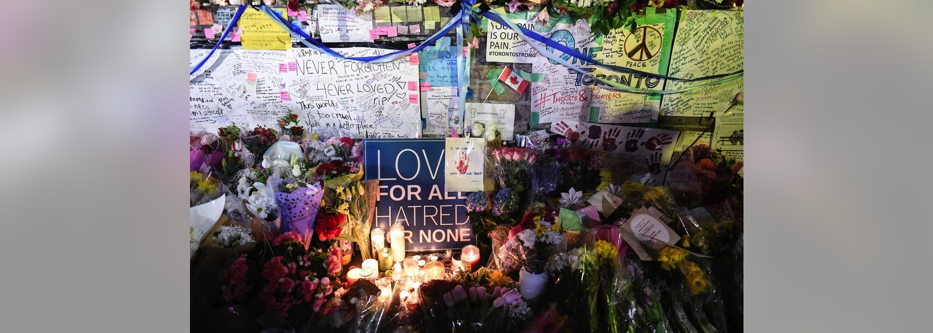 Flowers, notes and candles are piled high at a vigil on Yonge Street in Toronto, Tuesday, April 24, 2018, after multiple people were killed and others injured in Monday's deadly attack in which a van struck pedestrians on a Toronto sidewalk. (Galit Rodan/The Canadian Press via AP)