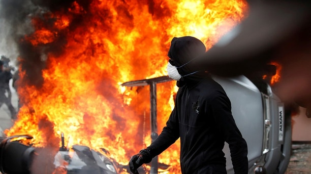 A masked protester walks near a car that burns outside a Renault automobile garage during clashes during the May Day labour union march in Paris, France, May 1, 2018.   REUTERS/Christian Hartmann - RC1DFADF7500