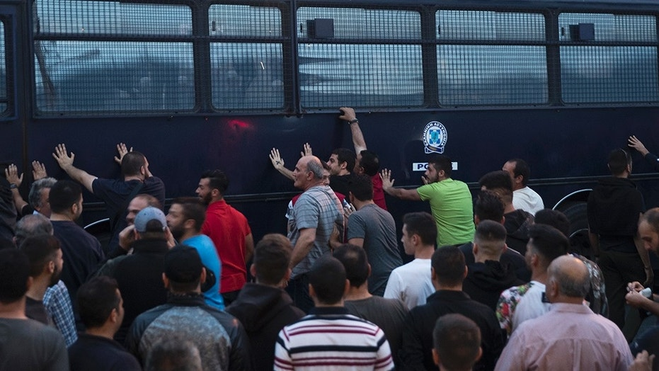 Protesters rock a riot police bus in the town of Mytilene on the northeastern Aegean island of Lesbos, Thursday, May 3, 2018. Police used tear gas to disperse the protesters who joined a demonstration against a visit to the island by Prime Minister Alexis Tsipras. Stores and services were also closed and at the government and European Union migration policy which has left thousands of migrants and refugees stranded on the island. (AP Photo/Petros Giannakouris)