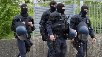 Masked police officers stand in a migrant shelter in Ellwangen, southern Germany, Thursday, May 3, 2018. Hundreds of police officers have raided a migrant shelter  after authorities were prevented from deporting a 23-year-old man from Togo days ago. (Stefan Puchner/dpa via AP)