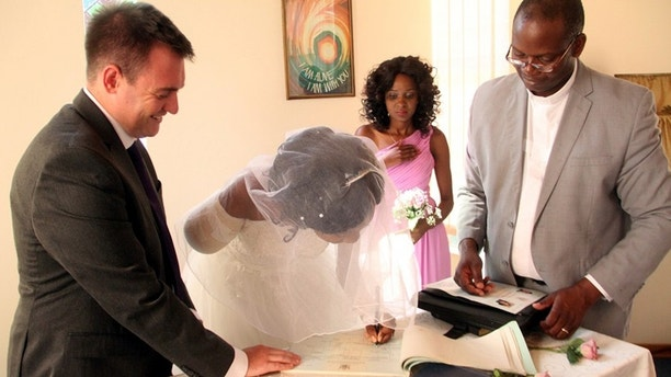 The bride Zanele Ndlovu signs a marriage certificate while the groom Jimmy Fox (left) and a pastor witness during a wedding held at a local hospital in Bulawayo yesterday. (picture by Nkosizile Ndlovu) ....