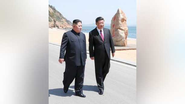 In this photo taken between May 7 and 8, 2018 released by Xinhua News Agency, Chinese President Xi Jinping, right, walks with North Korean leader Kim Jong Un during a meeting in Dalian in northeastern China's Liaoning Province. (Ju Peng/Xinhua via AP)