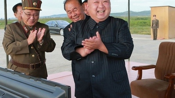 """FILE - In this undated file photo distributed on Sept. 16, 2017, by the North Korean government, North Korean leader Kim Jong Un, right, celebrates what was said to be the test launch of an intermediate range Hwasong-12 missile at an undisclosed location in North Korea. North Korea says it will never give up its nuclear weapons as long as the United States and its allies continue their """"blackmail and war drills"""" at its doorstep. Independent journalists were not given access to cover the event depicted in this image distributed by the North Korean government. The content of this image is as provided and cannot be independently verified. (Korean Central News Agency/Korea News Service via AP, File)"""