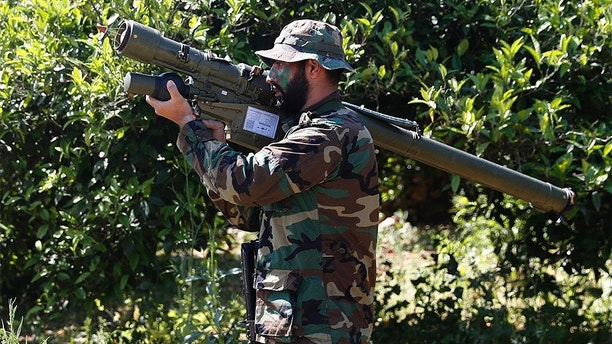 FILE - This April 20, 2017 file photo, shows a Hezbollah fighter holding an Iranian-made anti-aircraft missile on the border with Israel, in Naqoura, south Lebanon. There may not be much Iran can do about President Donald Trump's withdrawal from the nuclear deal with Iran, but across the Middle East, the Islamic Republic has a variety of ways it can hit back at the United States and America's regional allies. Southern Lebanon's rolling hills bordering Israel are considered a playground for Tehran through its Lebanese proxy militia Hezbollah. (AP Photo/Hussein Malla, File)