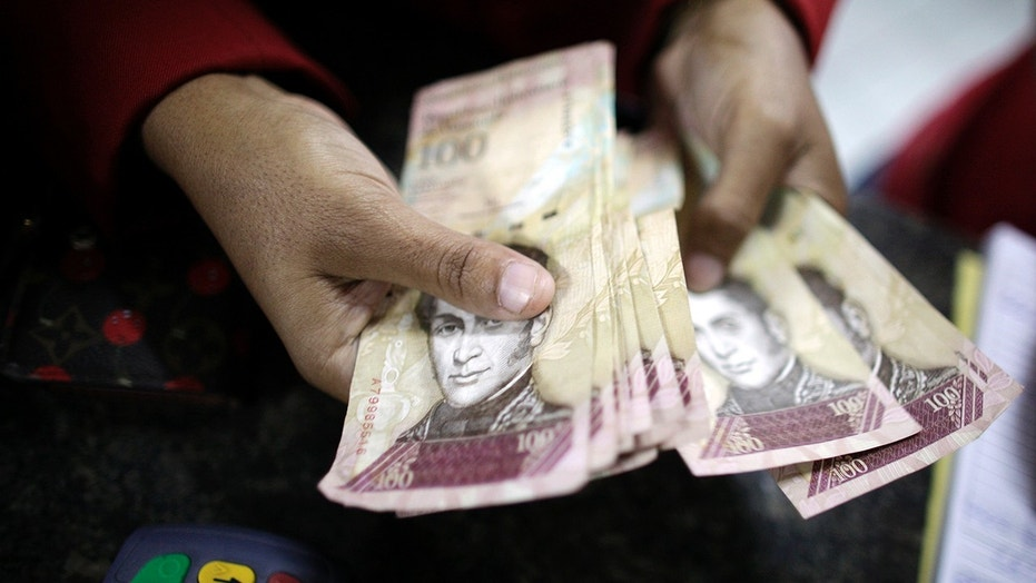 A woman counts bolivar notes as she pays for an electronic item at an store in La Guaira.