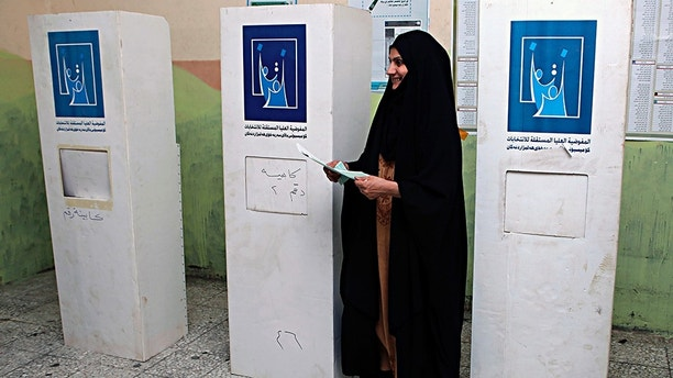 An Iraqi woman prepares to casts her vote in the country's parliamentary elections in Basra, 340 miles (550 kilometers) southeast of Baghdad, Iraq, Saturday, May 12, 2018. Polls opened across Iraq on Saturday in the first national election since the declaration of victory over the Islamic State group. (AP Photo/Nabil al-Jurani)