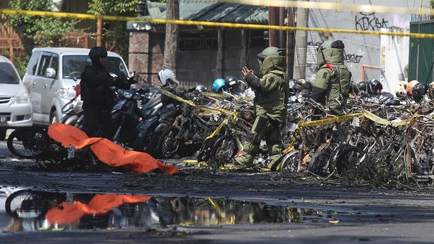 Members of police bomb squad inspect the wreckage of motorcycles at the site where an explosion went off outside a church in Surabaya, East Java, Indonesia, Sunday, May 13, 2018. Almost simultaneous attacks including one by a suicide bomber disguised as a churchgoer targeted churches in Indonesia's second largest city of Surabaya early Sunday, killing a number of people and wounding dozens, police said. (AP Photo/Trisnadi)