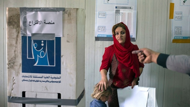 A volunteer points out the place where a displaced woman from Sinjar can cast her vote in the parliamentary elections, at a polling site in a camp for displaced people outside Irbil, Iraq, Saturday, May 12, 2018. Polls opened across Iraq on Saturday in the first national election since the declaration of victory over the Islamic State group. (AP Photo/Bram Janssen)