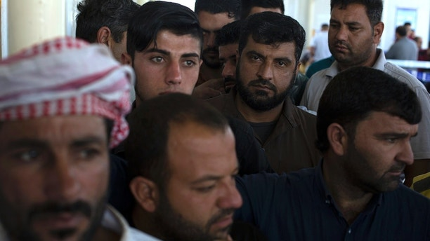 Displaced men from Mosul wait in a queue before casting their ballot in the parliamentary elections at a polling site in a camp for displaced people in Baharka, Iraq, Saturday, May 12, 2018. Polls opened across Iraq on Saturday in the first national election since the declaration of victory over the Islamic State group. (AP Photo/Bram Janssen)