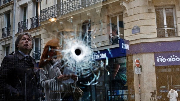 A bullet hole seen on the window of a cafe located near the area where the assailant of a knife attack was shot dead by police officers, in central Paris, Sunday May 13, 2018. The man behind a deadly knife attack in central Paris was born in Chechnya and had been on police radar for radicalism, and his parents have been detained for questioning, French authorities said Sunday. (AP Photo/Thibault Camus)