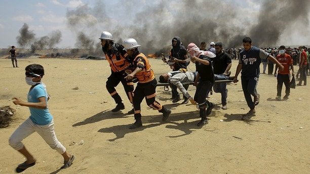 Palestinian medics and protesters evacuate a wounded youth during a protest at the Gaza Strip's border with Israel, east of Khan Younis, Gaza Strip, Monday, May 14, 2018. Thousands of Palestinians are protesting near Gaza's border with Israel, as Israel prepared for the festive inauguration of a new U.S. Embassy in contested Jerusalem. (AP Photo/Adel Hana)