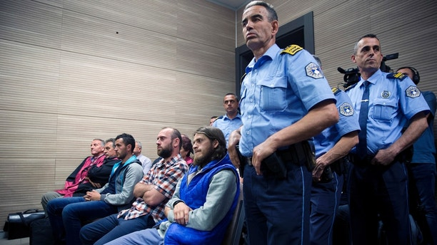 Kosovo police officers stand guard next to from far left, Burim Istrefi, Kenan Plakaj and Arton Ahmeti in court for the foiled attack against the Israeli team in a 2016 qualifying World Cup match in neighboring Albania, in Kosovo's capital Pristina on Friday, May 18, 2018. A Kosovo court has sentenced nine Albanians from a fine to 10 years of jail for planning an attack against the Israeli team in a 2016 qualifying World Cup match. The group, also with members in Albania and Macedonia, was coordinated by two Albanians part of the IS terror group in Syria to hold the attack in November 2016. Police found explosive devices, weapons, electronic equipment and extremist religious literature at their homes.  (AP Photo/Visar Kryeziu)