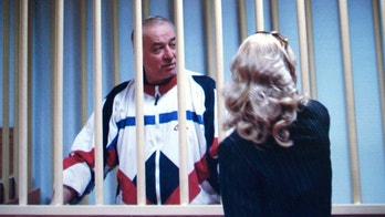 Sergei Skripal speaks to his lawyer from behind bars seen on a screen of a monitor outside a courtroom in Moscow on Wednesday, Aug. 9, 2006. Skripal a retired Russian colonel recruited by British intelligence in the mid-1990s was sentenced Wednesday by a military court in Moscow to 13 years imprisonment for spying, officials said. (AP Photo/Misha Japaridze)