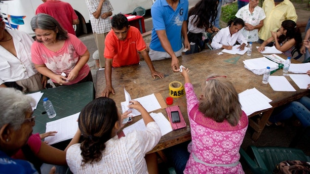 """Voters register with members of the ruling United Socialist Party before proceeding to a polling post to vote in presidential elections in Valencia, Venezuela, Sunday, May 20, 2018. Known as """"red points' the checkpoints are set up outside voting centers to confirm peoples' cards, which are needed to access social programs. President Nicolas Maduro is seeking a second six-year term, despite a deepening crisis that's made food scarce and inflation soar as oil production in the once wealthy nation plummets.(AP Photo/Fernando Llano)"""