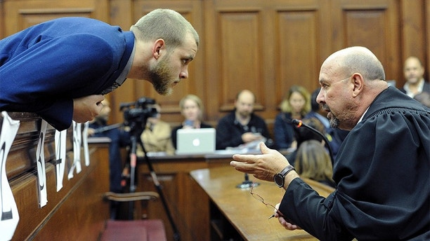 Henri van Breda, left, talks to one of his legal adviser, Piet Botha, right, in the HIgh Court in Cape Town, South Africa, Monday, May 21, 2018 as he awaits the verdict in his murder, and attempted murder trial. Van Breda is accused of murdering his father, mother and brother and the attempted murder of his sister. (AP Photo/Nasied Manie)