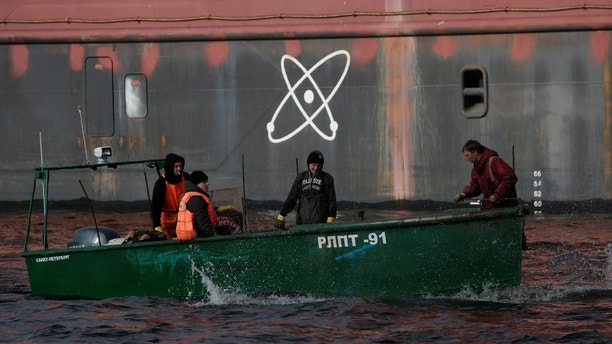 """Fishermen sail on a boat past the floating nuclear power plant """"Akademik Lomonosov"""", which is towed to an Atomflot base in Murmansk for nuclear fuel loading, in St. Petersburg, Russia April 28, 2018. REUTERS/Anton Vaganov - RC1752884410"""
