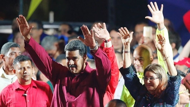 Venezuela's President Nicolas Maduro and his wife Cilia Flores wave to supporters at the presidential palace in Caracas, Venezuela, Sunday, May 20, 2018. Electoral officials declared the socialist leader the winner of Sunday's presidential election, while his leading challenger questioned the legitimacy of a vote marred by irregularities and called for a new ballot to prevent a brewing social crisis from exploding. (AP Photo/Ariana Cubillos)