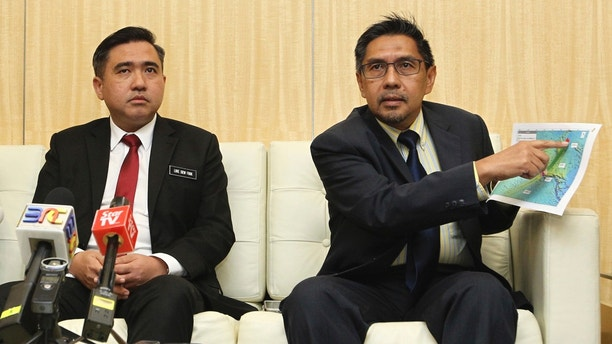"""Director general of the Malaysian Department of Civil Aviation, Azharuddin Abdul Rahman, right, shows the search area map during a press conference as Malaysia new Transport Minister Anthony Loke Siew Fook looks on in Putrajaya, Malaysia on Wednesday, May 23, 2018. New Transport Minister Anthony Loke says the search for missing Malaysia Airline Flight 370 ends next Tuesday after a 90-day period under a """"no cure no fee"""" agreement with a private U.S. firm. (AP Photo)"""