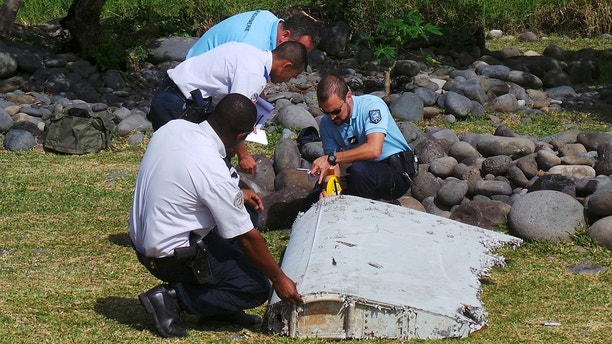 File picture shows French gendarmes and police inspecting a large piece of plane debris which was found on the beach in Saint-Andre, on the French Indian Ocean island of La Reunion, July 29, 2015. French prosecutor announced on Thursday that we can say with certainty that the wing part found on Saint-Andre beach was from missing Malaysia Airlines Flight MH370.  REUTERS/Zinfos974/Prisca Bigot/Files     TPX IMAGES OF THE DAY     - LR2EB93176LD7