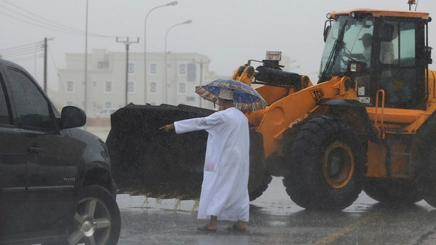 """An Omani official gestures to a loader driver to tear away a road median to drain a flooded street in Salalah, Oman, Friday, May 25, 2018. Cyclone Mekunu will be """"extremely severe"""" when it crashes into the Arabian Peninsula this weekend, meteorologists warned Friday, after earlier thrashing the Yemeni island of Socotra. (AP Photo/Kamran Jebreili)"""