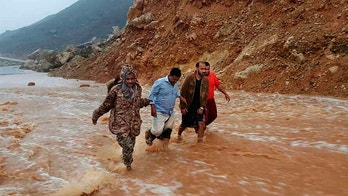 Men walk on a road flooded after heavy rain and strong winds caused damage in Hadibu as Cyclone Mekunu pounded the Yemeni island of Socotra, Thursday, May 24, 2018. At least 17 people were reported missing. The powerful storm remained on path to strike Oman this weekend. (AP Photo/Abdullah Morgan)