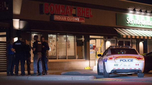 Police stand outside the Bombay Bhel restaurant in Mississauga, Canada Friday May 25, 2018. Canadian police say an explosion set off deliberately in a restaurant has wounded a number of people. (Doug Ives/The Canadian Press via AP)