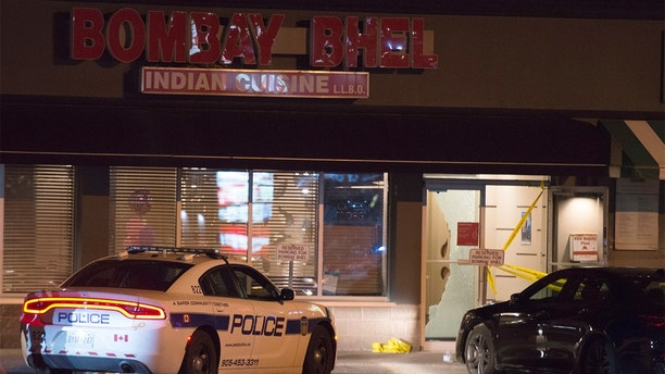 Police stand in front of the Bombay Bhel restaurant in Mississauga, Canada on May 25, 2018 Restaurant has wounded a number of people. (Doug Ives / The Canadian Press on AP)