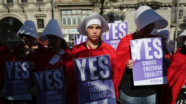 Volunteers from Reproductive rights, against Oppression, Sexism & Austerity (ROSA) dressed as characters from 'The Handmaid's Tale', demonstrate in Dublin, Wednesday May 23, 2018, calling for a 'Yes' vote in Ireland's upcoming abortion referendum on Friday. (Niall Carson/PA via AP)